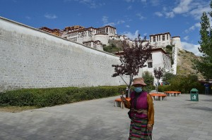 Woman with prayer wheel by Potala Palace